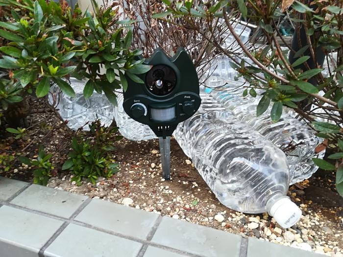 花壇に超音波機器とペットボトルを設置してる画像